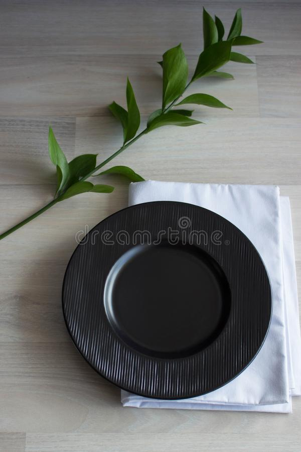 Black plate on white wooden background. With plant and napkin,top view. Empty plate for serving.  royalty free stock photography