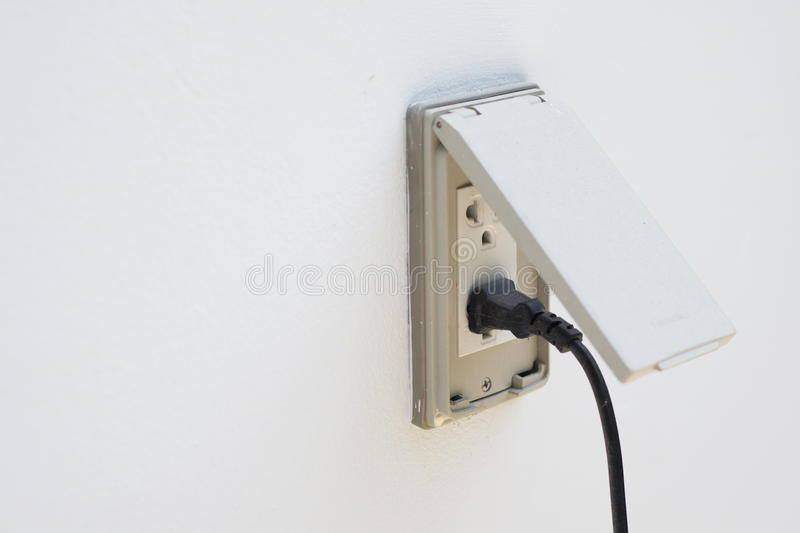 Black plug plugged in a socket with cover. For outdoor stock image