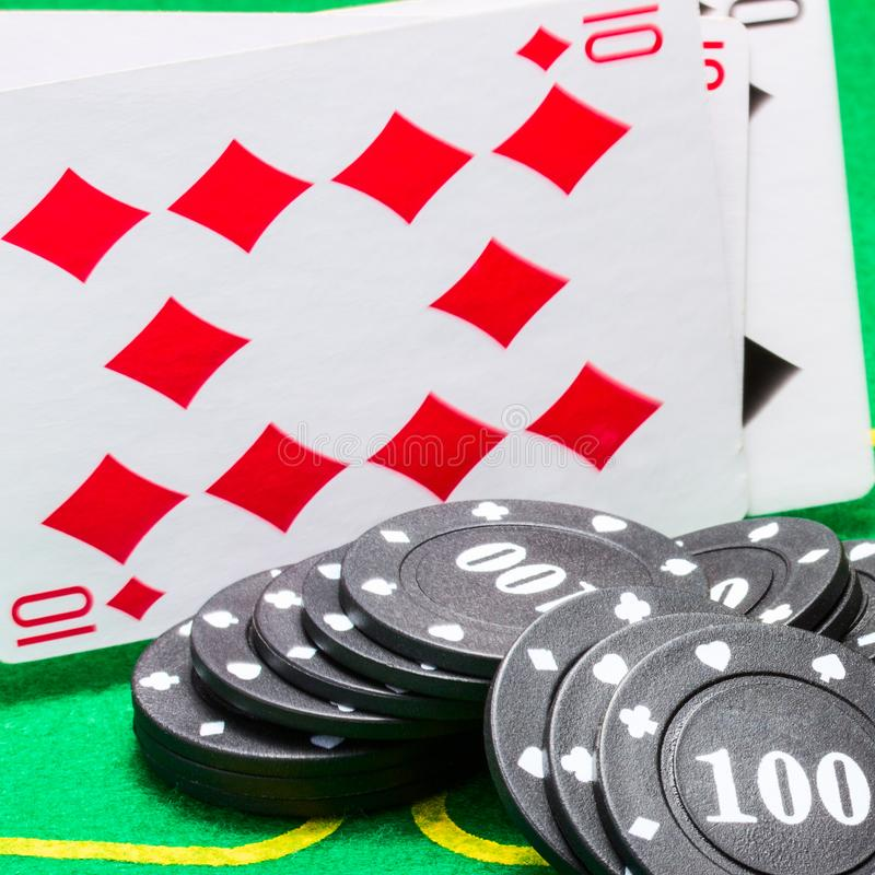 Black poker chips and falling playing cards closeup stock photos