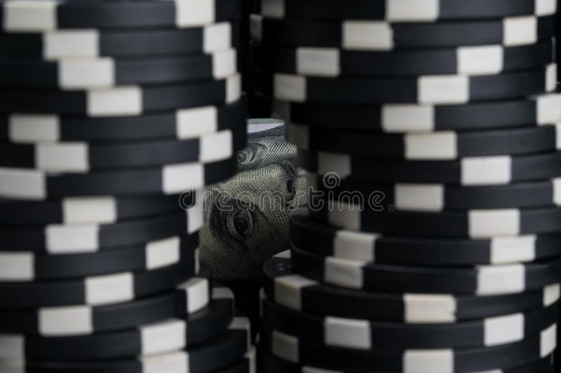 Black poker chips stand in front of money, closeup royalty free stock image