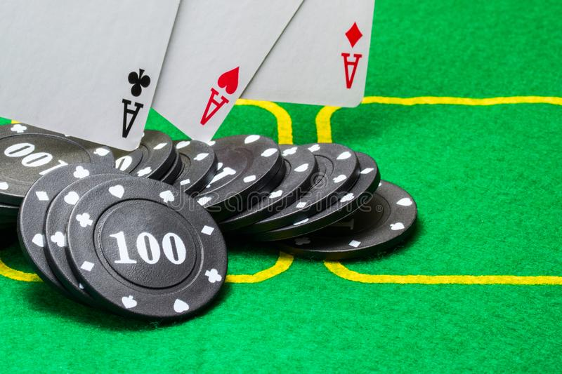 Black poker chips on which three aces fall royalty free stock images