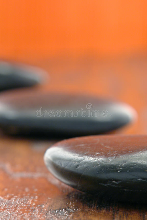Black polished Hot Massage Stones on Wood in a Spa stock photo