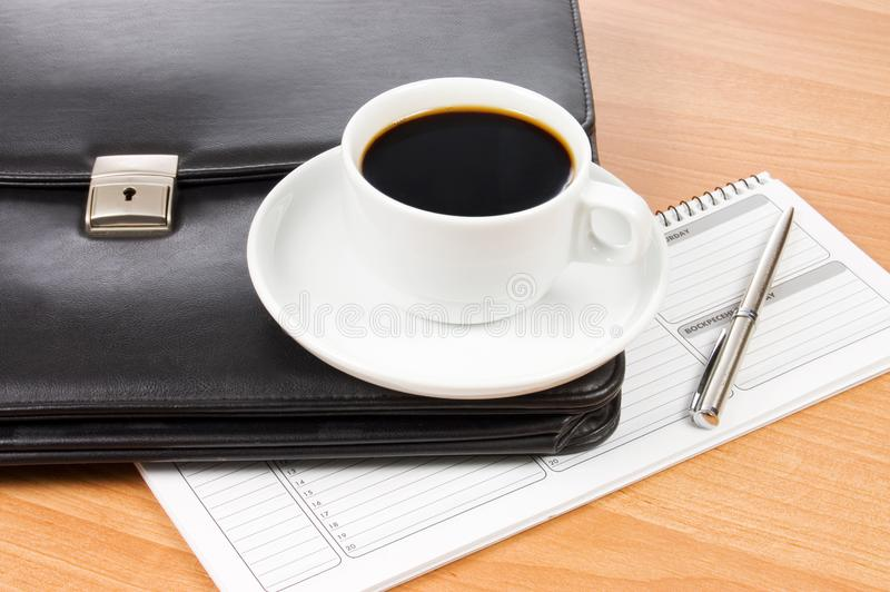 Black portfolio and coffee on a table stock photography