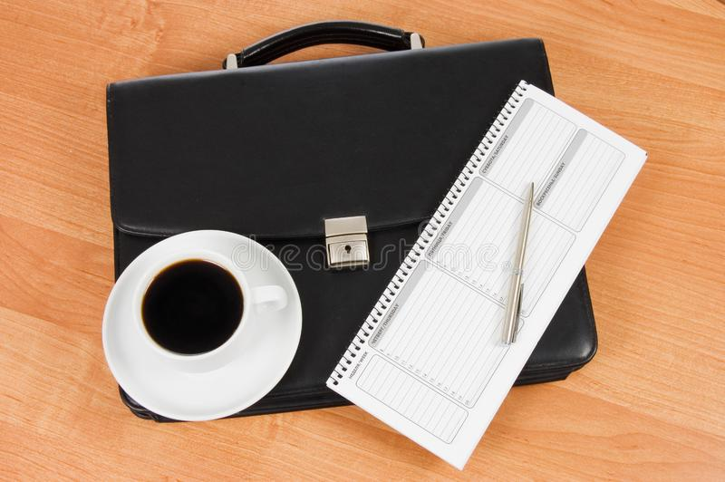 Black portfolio and coffee on a table stock images