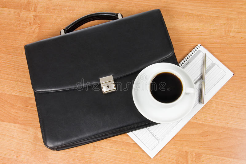 Black portfolio and coffee on a table royalty free stock photos
