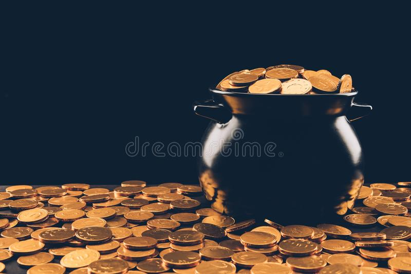 Black pot with golden coins. Isolated on black, st patricks day concept stock photo