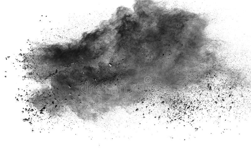 Black powder explosion against white background. The particles of charcoal splattered on white background. Closeup of black dust particles explode isolated on stock image