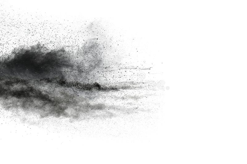 Black powder explosion. The particles of charcoal splatter on white background. Closeup of black dust particles splash isolated on background stock image