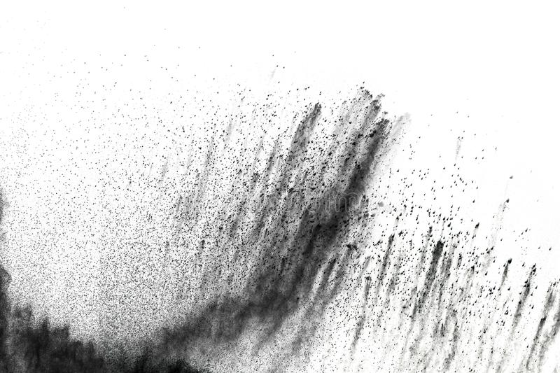 Black powder explosion. The particles of charcoal splatter on white background. Closeup of black dust particles splash isolated on background stock photo
