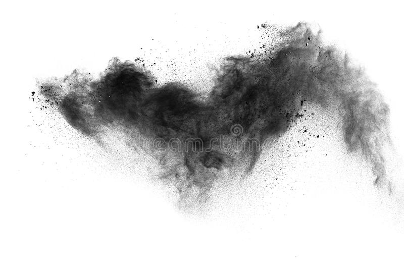 Black powder explosion. The particles of charcoal splatter on white background. Closeup of black dust particles splash isolated on background royalty free stock photography