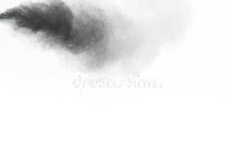 Black powder explosion. The particles of charcoal splatter on white background. Closeup of black dust particles splash isolated on background royalty free stock image