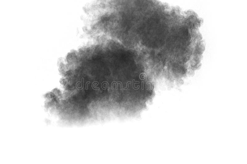 Black powder explosion. The particles of charcoal splatter on white background. Closeup of black dust particles splash isolated on background royalty free stock photo