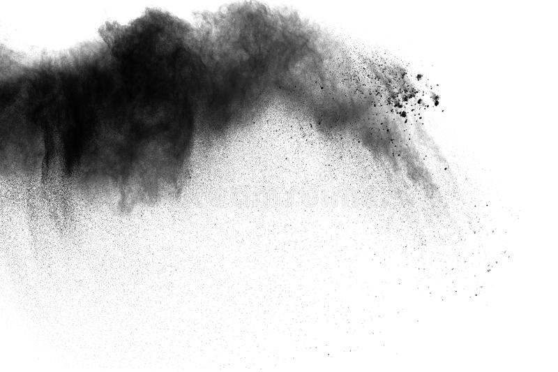 Black powder explosion. The particles of charcoal splatter on white background. Closeup of black dust particles splash isolated on background royalty free stock images
