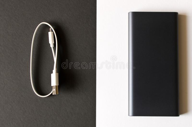 Black power Bank with adapter for charging mobile devices on a black white background stock photo