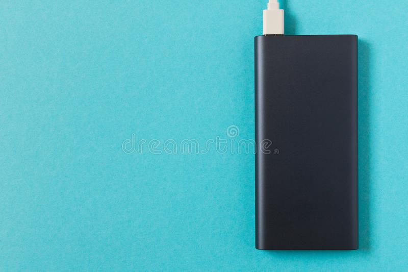 Black power Bank with adapter for charging mobile devices on a blue background.  royalty free stock photo
