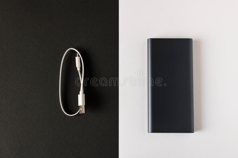 Black power Bank with adapter for charging mobile devices on a black white background.  stock images