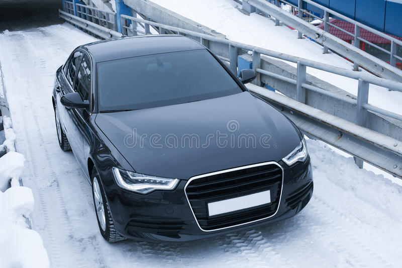 Black prestigious car on snow stock image