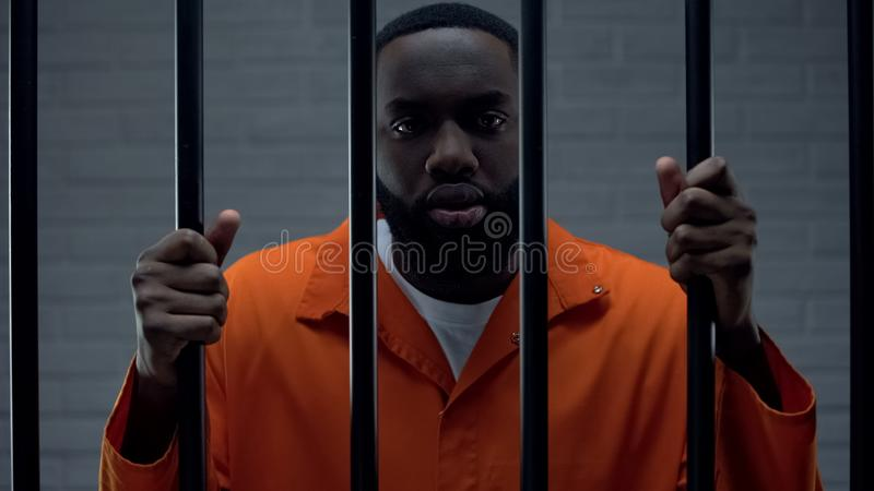 Black prisoner holding bars and looking at camera, drug dealer punishment royalty free stock photo