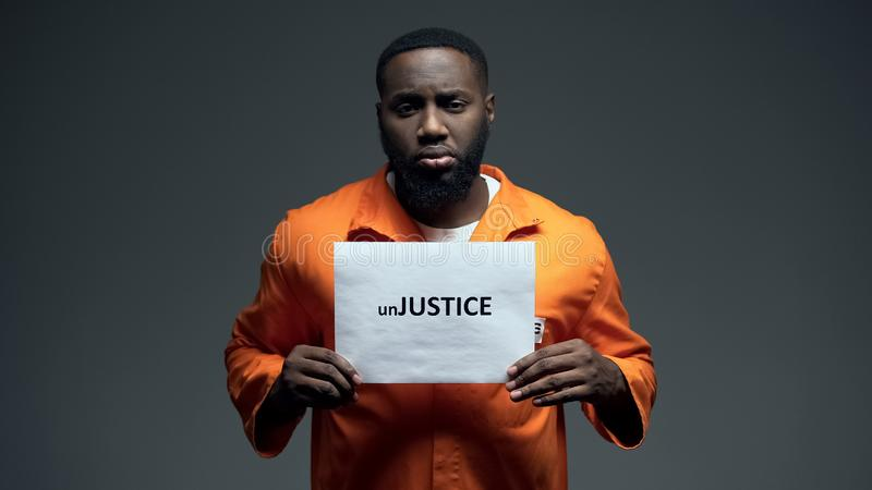 Black prisoner holding unjustice sign in cell, human rights protection awareness. Stock photo royalty free stock images