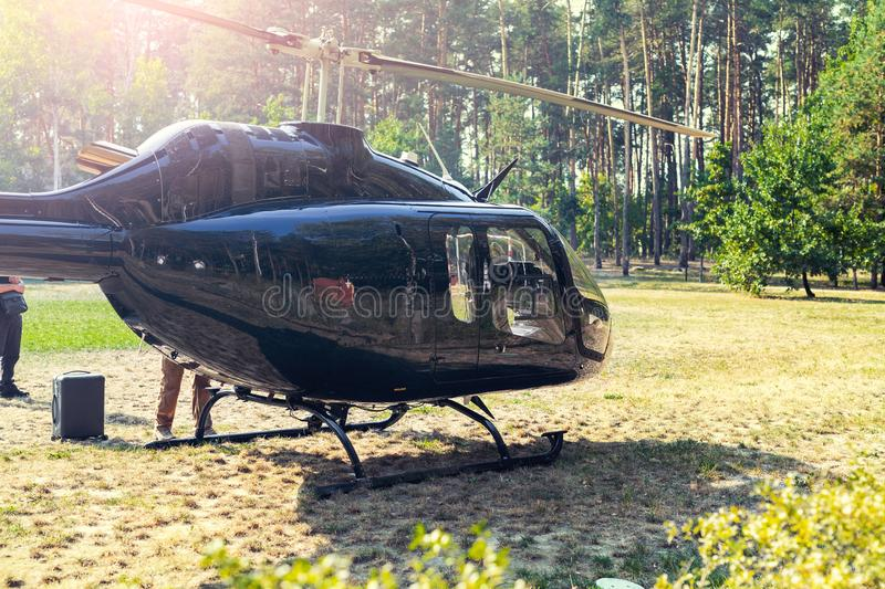 Black private modern luxury helicopter standing on grass field near forest at country rural landscape. Rich buiness lifestyle royalty free stock photos