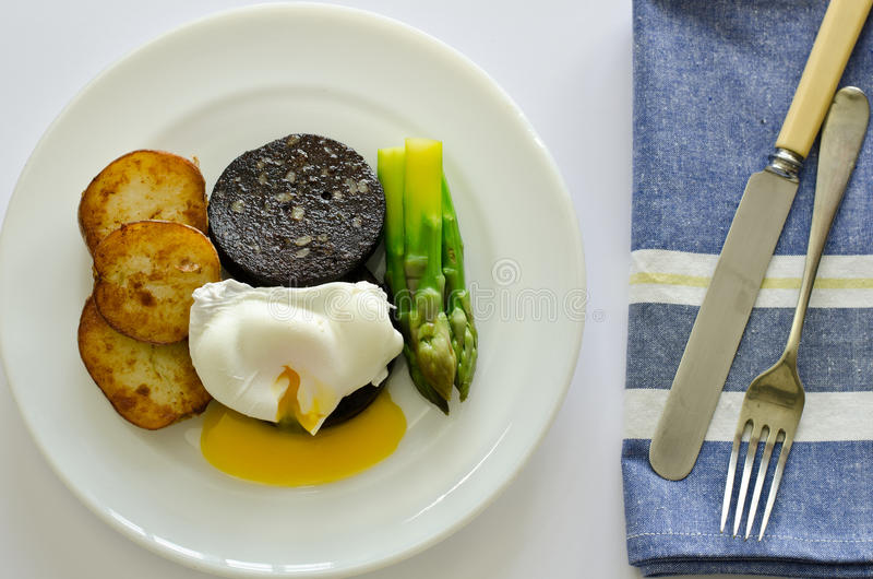 Black pudding with poached egg and asparagus. A meal of black pudding and poached egg with asparagus and saute potatoes with runny egg yolk stock photos