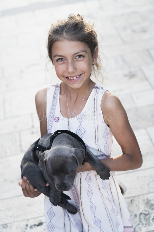 Black puppy playing with a girl. Puppy with girl spend a day at the outdoor playing and having fun. Concept of love for nature, protection of animals,innocence stock photography