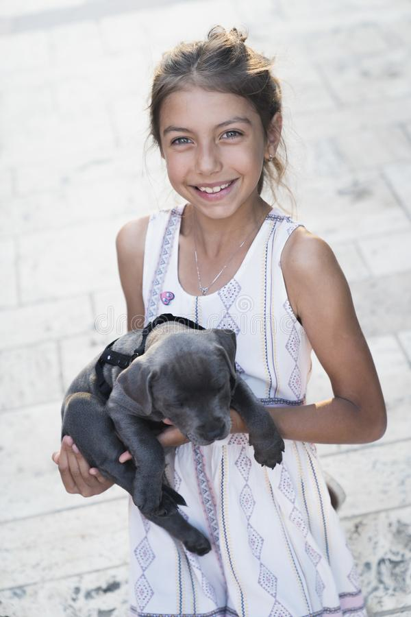 Black puppy playing with a girl. Puppy with girl spend a day at the outdoor playing and having fun. Concept of love for nature, protection of animals,innocence stock photos