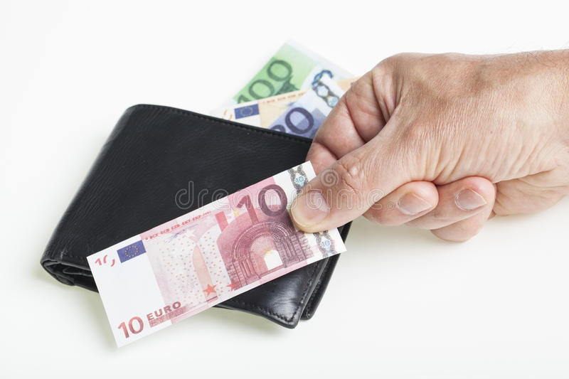 Black purse and hand. Black purse and male hand holding a miniature play money euro banknote on a white background. Financial concept for capital loss and stock photography