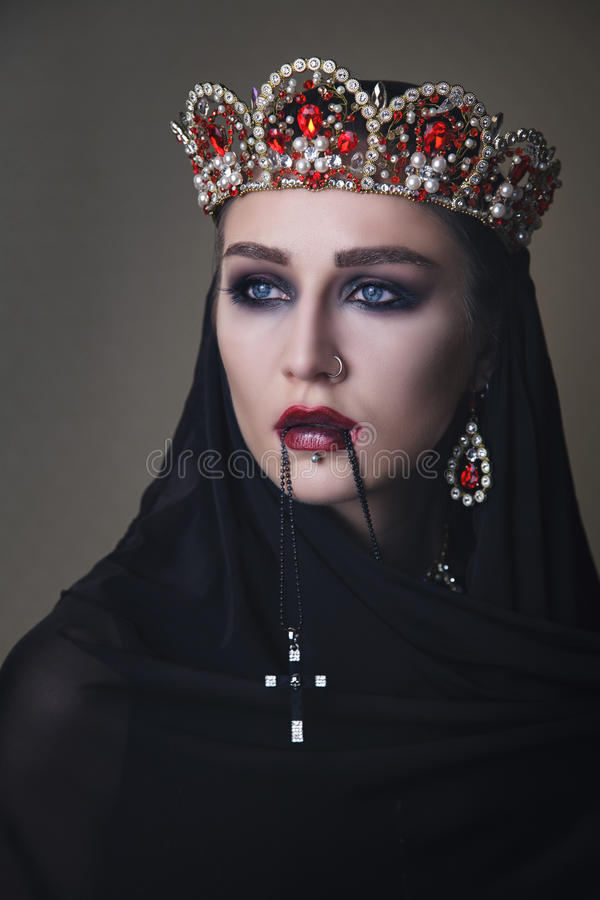 Black queen in a crown and with a crucifix royalty free stock image