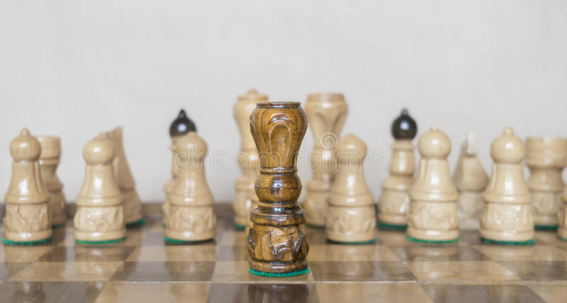 Black queen in front of white figures on chess table stock photo