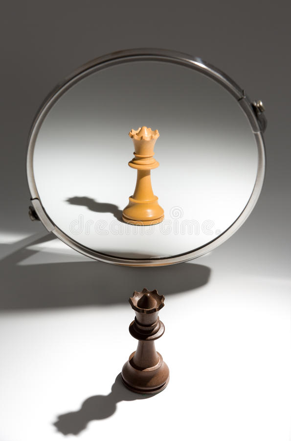 A black queen is looking in a mirror to see herself as a white queen. stock photos