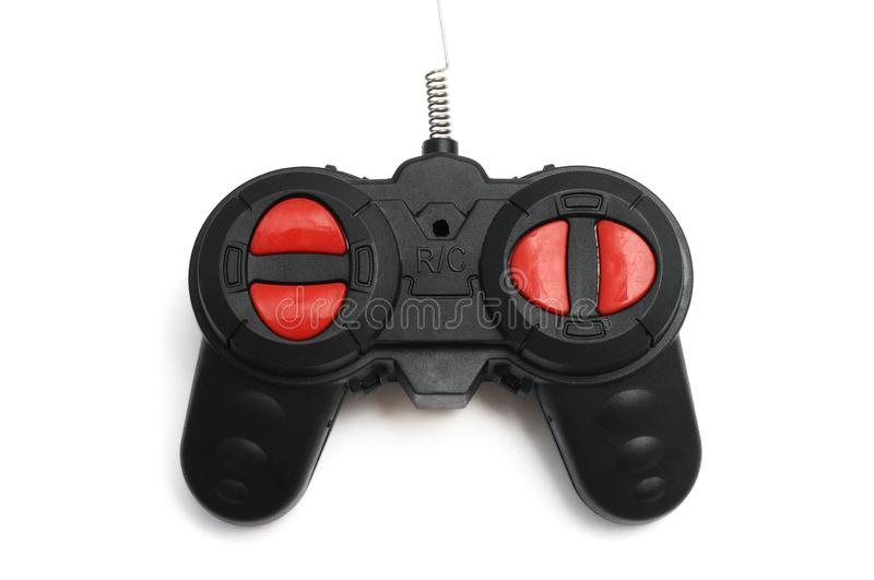 A black radio control RC remote controller with red buttons and a fine antenna. A closeup photo taken on a black radio control RC remote controller with red stock image