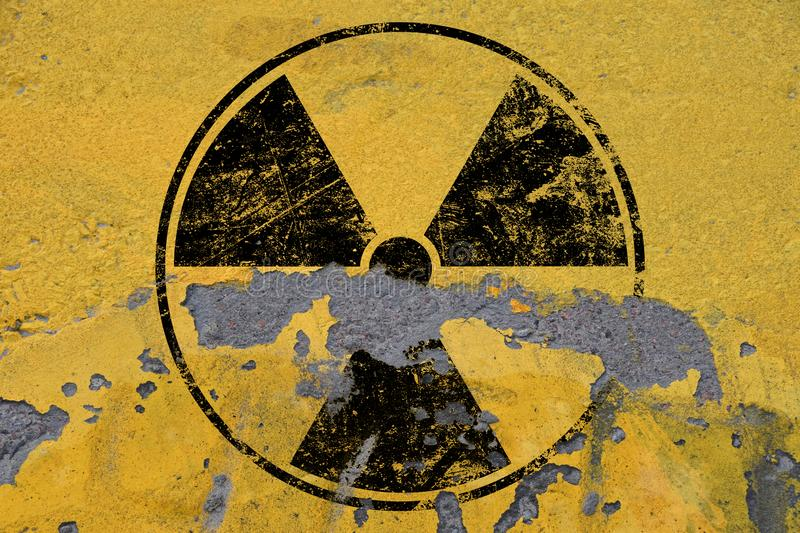 Black radioactive sign over yellow background. Black radioactive hazard warning sign painted over grunge yellow background with copy space royalty free stock images