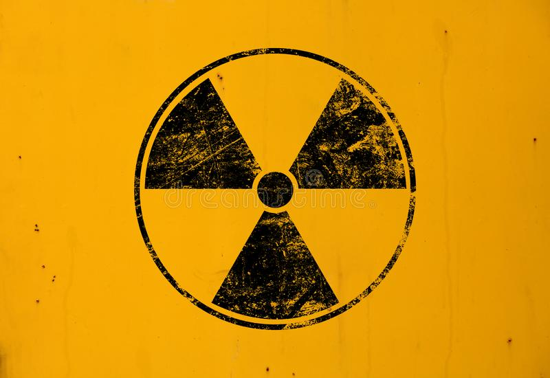 Black radioactive sign over yellow background. Black radioactive hazard warning sign painted over grunge yellow metal wall background with copy space stock images