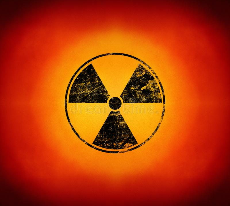 Black radioactive sign over yellow background. Black radioactive hazard warning sign painted over grunge yellow and red background with copy space stock image