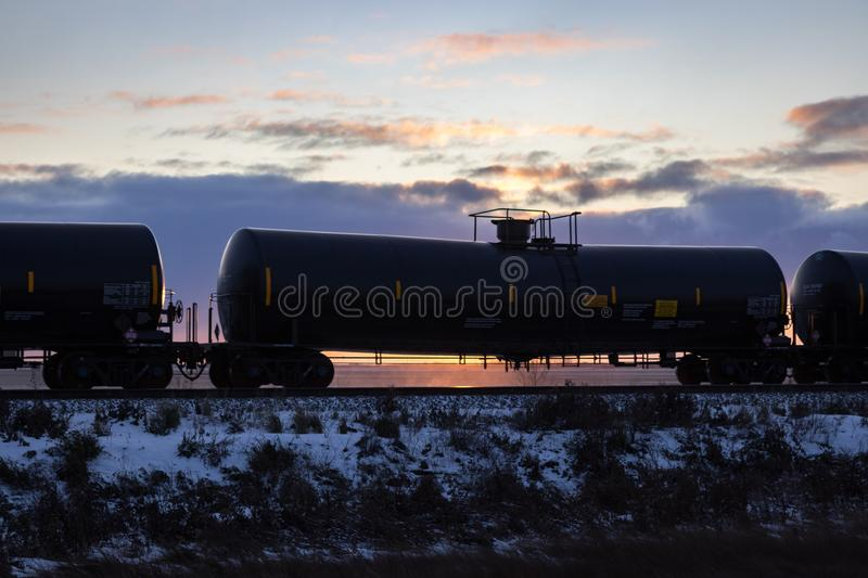 Black Railroad Tank Car Silhouetted at Sunset. Black Railroad Tank Car Silhouetted against Sunset stock images