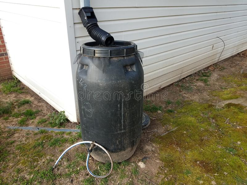 Black rain barrel with gutter downspout and hose stock photos