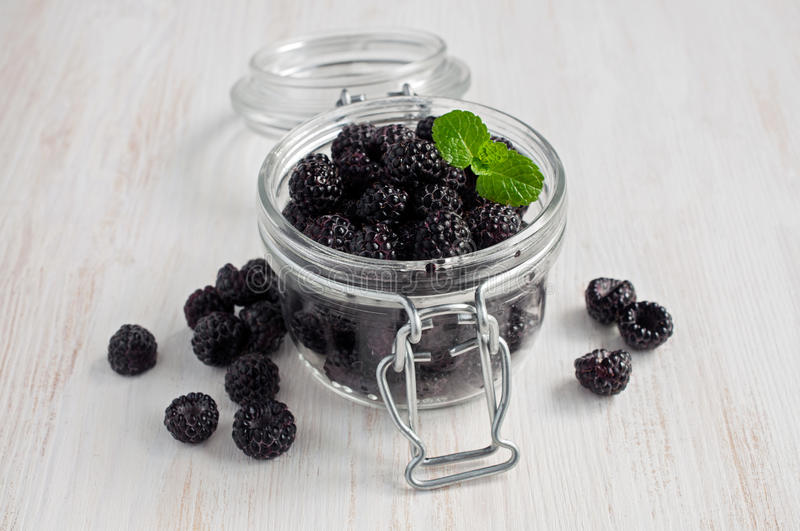 Black raspberry or blackberry in glass jar royalty free stock photography