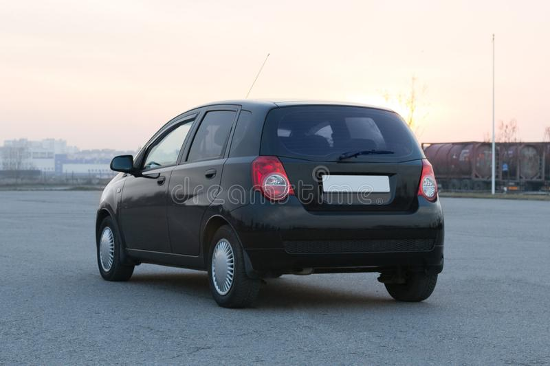 Black rear view compact modern city car. Photo exterior auto royalty free stock image