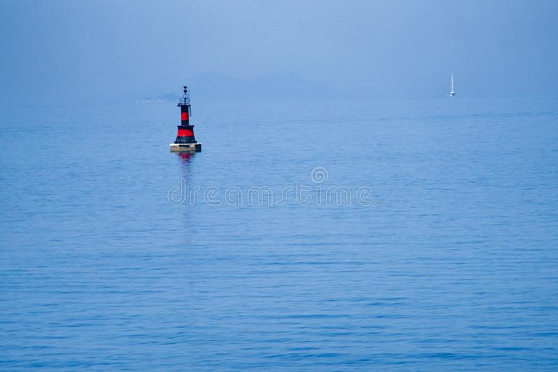 Black-red buoy. Sailing boat in the background royalty free stock photo