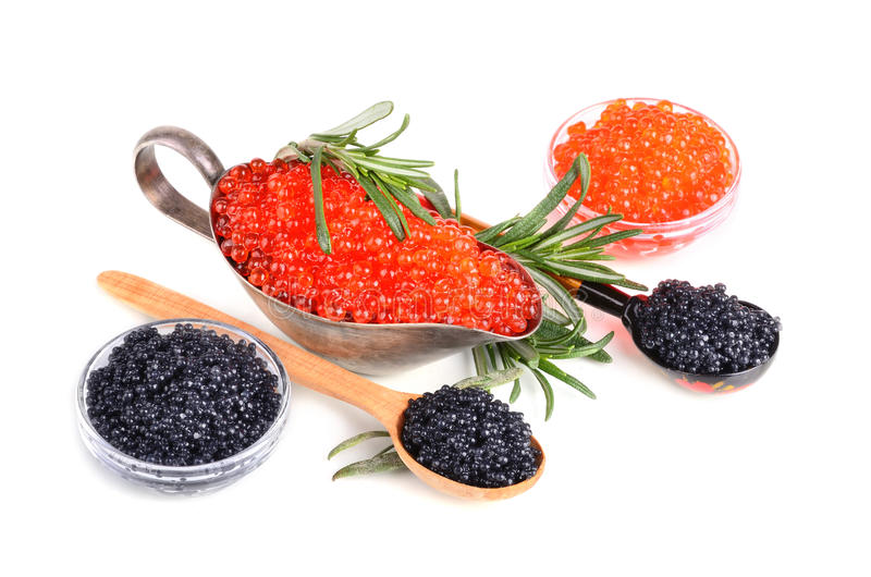 Black and red caviar. In glass bowls and in silver sauceboat on a white background royalty free stock photography