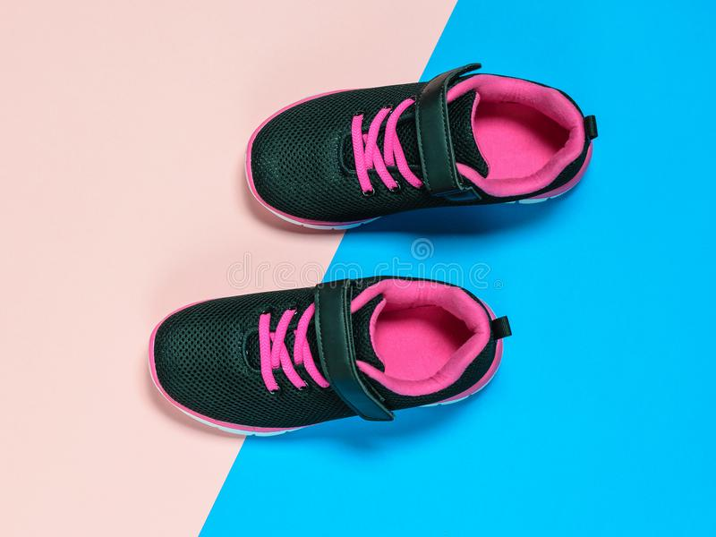 Black with red children`s sneakers on a pastel background. royalty free stock images