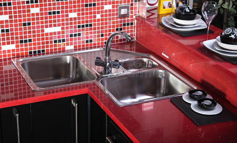 Black and red counter top in kitchen whit sink royalty free stock photo