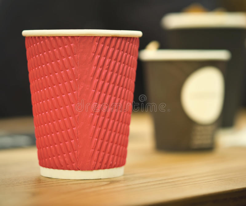 Black and red craft paper coffee cups in cafe on wooden table. Lifestyle, coffeeshop concept. royalty free stock photo