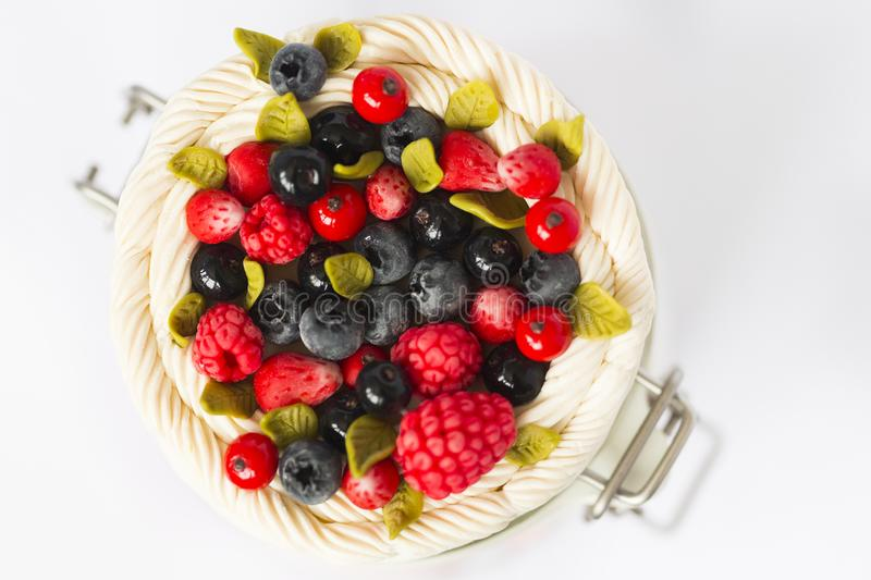 Black and red currant berries, raspberries and strawberries and green mint leaves in whipping cream. All made of polymer clay on the top of glass jar royalty free stock photo