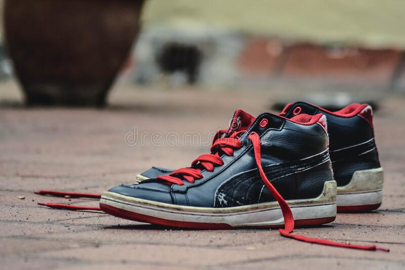 Black and Red Leather Puma Lace Up High Top Shoes stock image