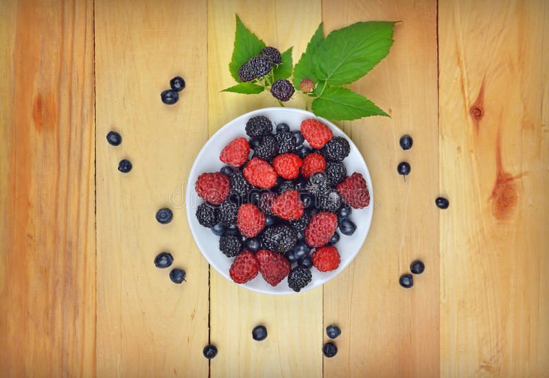 Black and red raspberries and blueberries on a wooden table. royalty free stock images