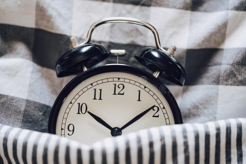 Black retro alarm clock sleeping on pillow with blanket metaphor of insomnia, late at work, well sleep with time countdown or wake stock image