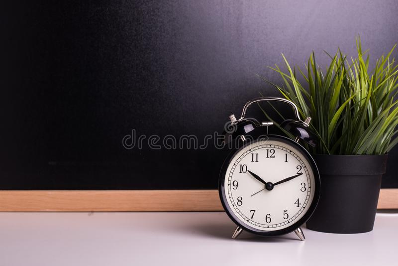 Vintage alarm clock on the background of a blackboard royalty free stock image