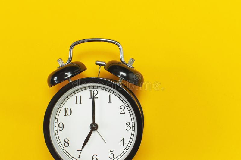 Black retro alarm clock on yellow background top view Flat lay copy space. Minimalistic background, concept of time, deadline,. Time to work, morning stock photo